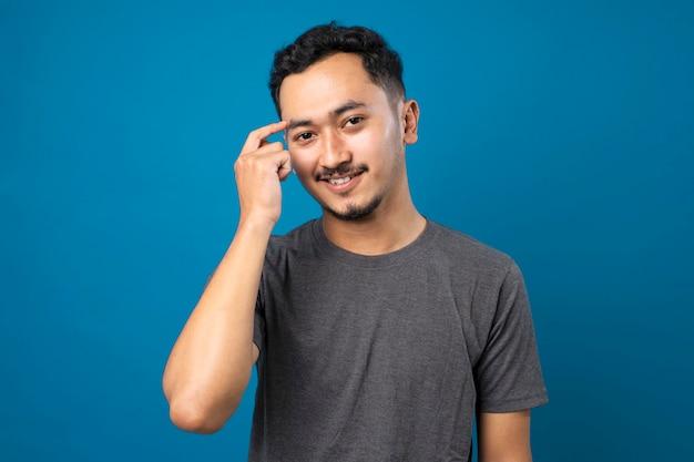 カジュアルなtシャツを着てひげを持つ若いハンサムな男人差し指を頭に笑顔