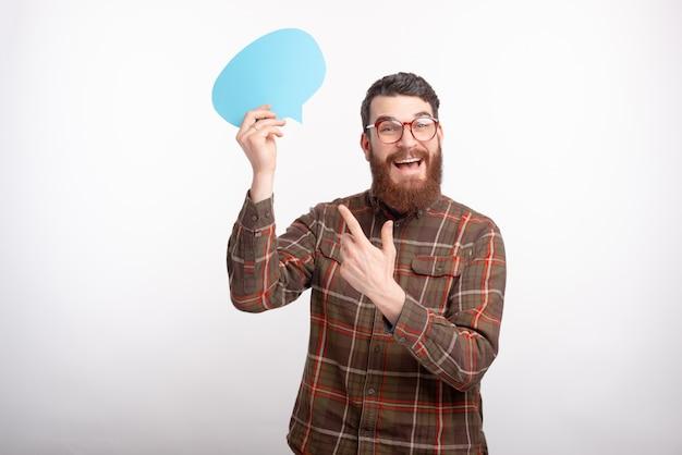 수염이 안경을 쓰고 연설 거품을 가리키는 젊은 잘 생긴 남자