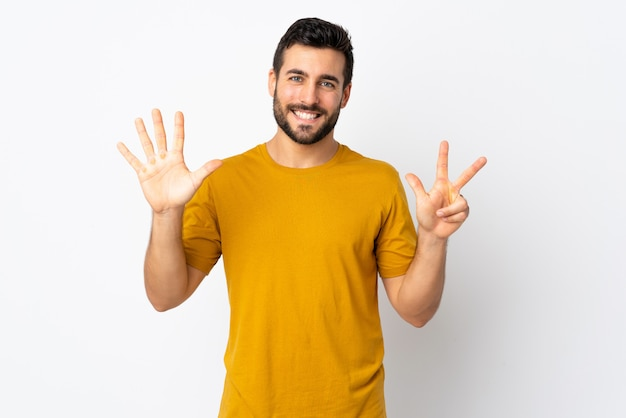 Young handsome man with beard on white wall counting eight with fingers