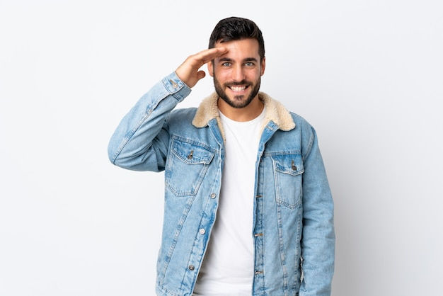 Young handsome man with beard on white wall saluting with hand with happy expression