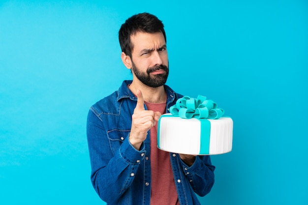 Young handsome man with a big cake over isolated blue wall frustrated and pointing to the front