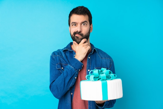 Young handsome man with a big cake over isolated blue wall having doubts and with confuse face expression