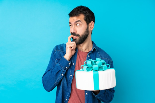 Young handsome man with a big cake over isolated blue wall nervous and scared