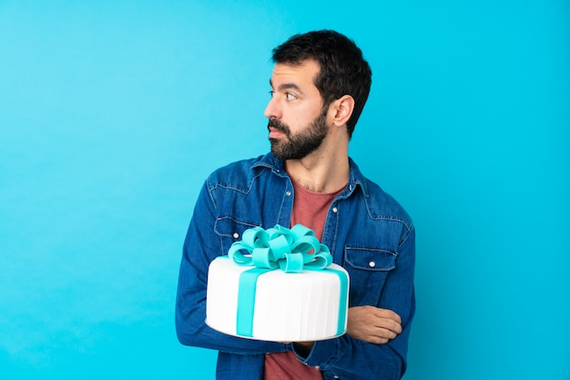 Young handsome man with a big cake over isolated blue wall portrait
