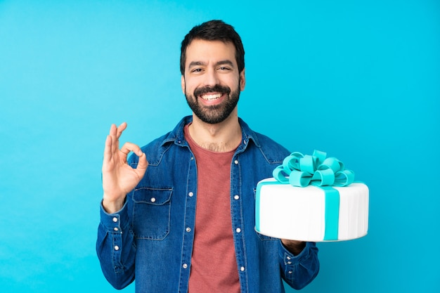 Young handsome man with a big cake over isolated blue wall showing an ok sign with fingers