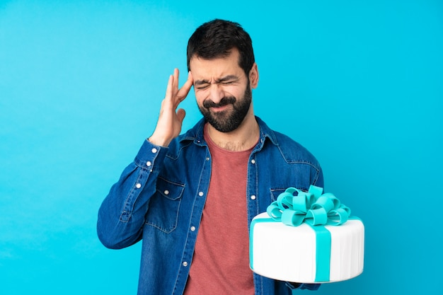 Young handsome man with a big cake over isolated blue wall with headache