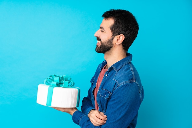Young handsome man with a big cake in lateral position