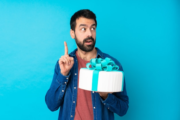 Young handsome man with a big cake thinking an idea pointing the finger up