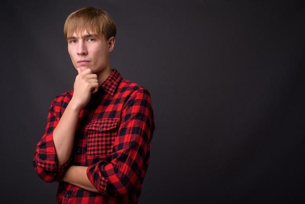 Молодой красавец со светлыми волосами на сером