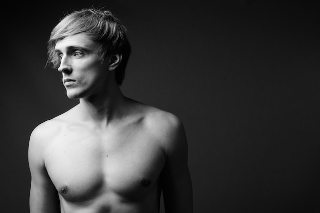 Young handsome man with blond hair shirtless in black and white