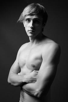 黒と白で上半身裸のブロンドの髪を持つ若いハンサムな男