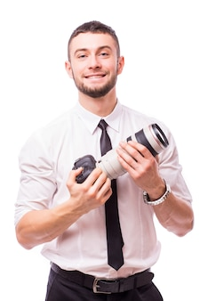 Young handsome man with camera isolated over white wall.