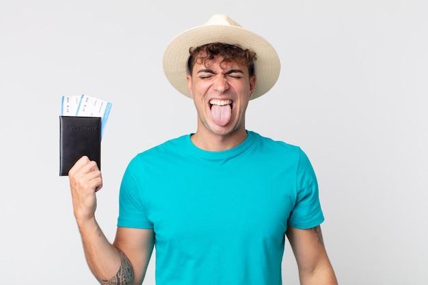 쾌활하고 반항적인 태도로 농담을 하고 혀를 내밀고 있는 젊고 잘생긴 남자. 여권을 들고 있는 여행자