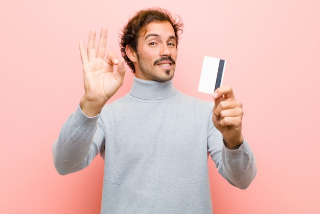 Young handsome man with a credit card against pink flat wall