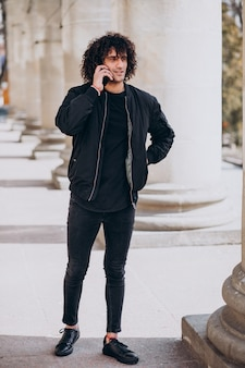Young handsome man with curly hair talking on the phone