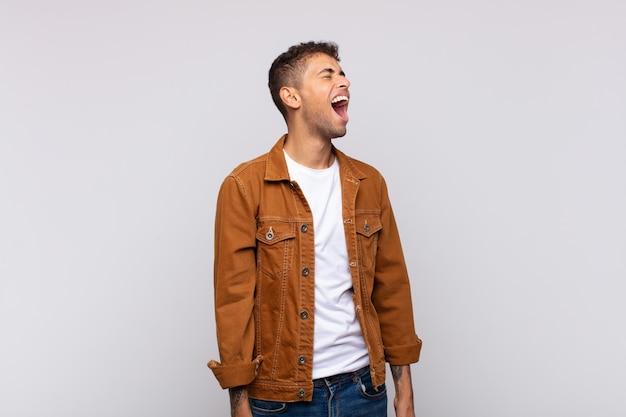 白い壁にポーズをとってデニム茶色のシャツと若いハンサムな男
