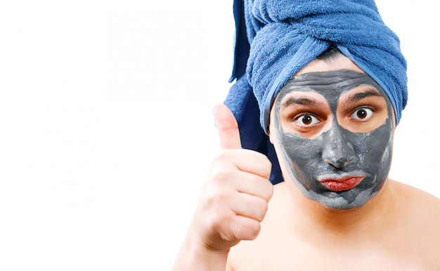 Young handsome man with facial mask shows with a gesture that everything is super