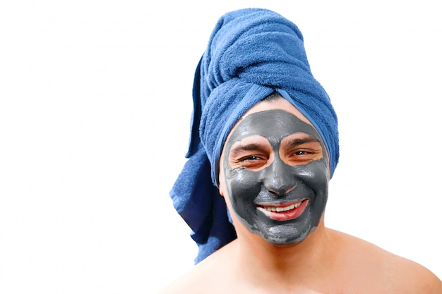 Young handsome man with facial mask smiling, isolated