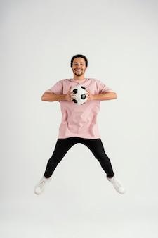 サッカーボールのジャンプと若いハンサムな男 Premium写真