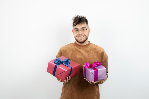 Giovane uomo bello con scatole regalo sentirsi felice.