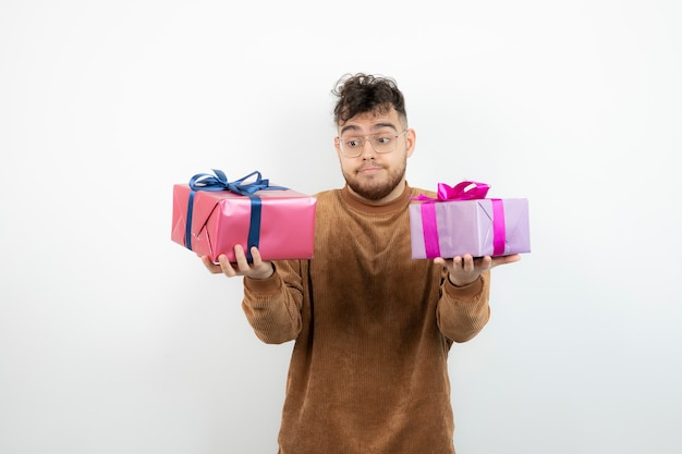 Young handsome man with gift boxes standing and posing.