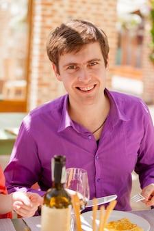 Молодой красавец с бокалом вина и блюдами в ресторане в летнее время.