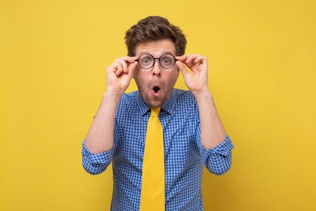眼鏡をかけた若いハンサムな男は、ショックを受け、驚き、驚きの表情をしています。