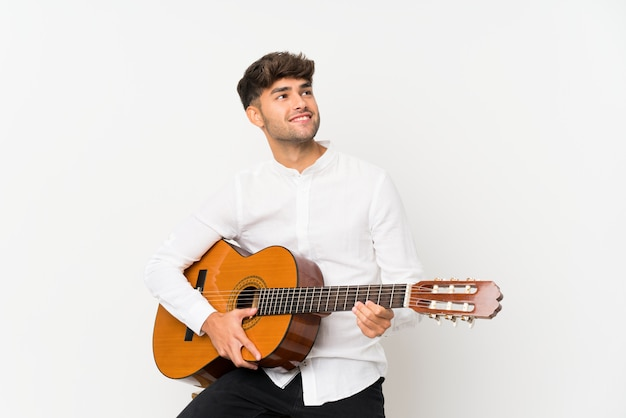 Young handsome man with guitar over isolated white wall looking up while smiling
