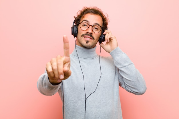Young handsome man with headphones against pink flat wall