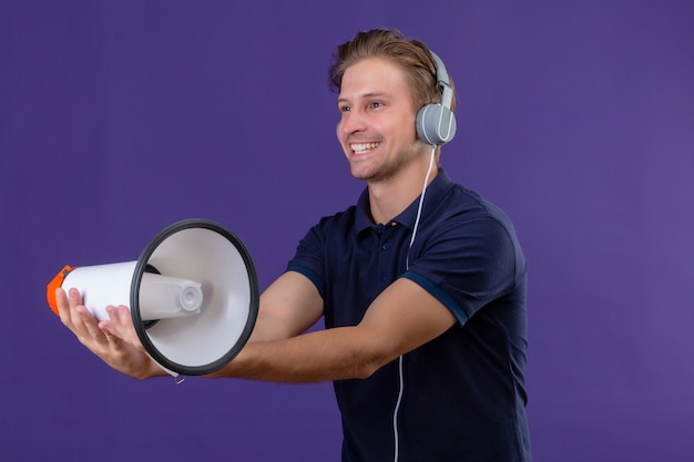 Young handsome man with headphones holding megaphone with big smile on face standing over purple background