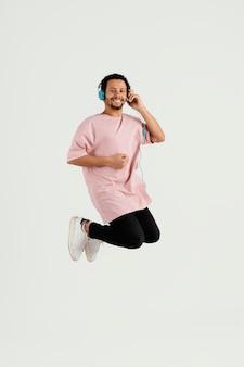 ジャンプするヘッドフォンを持つ若いハンサムな男 Premium写真