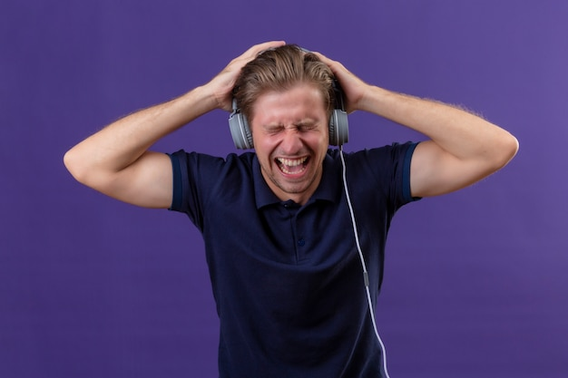 Young handsome man with headphones screams while listens music with high volume standing over purple background