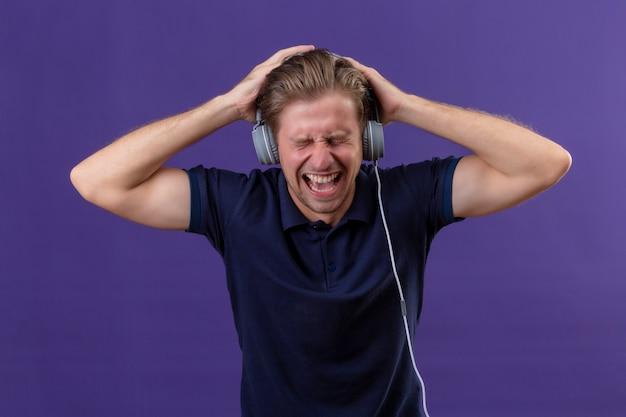 Giovane uomo bello con le cuffie urla mentre ascolta musica ad alto volume in piedi su sfondo viola