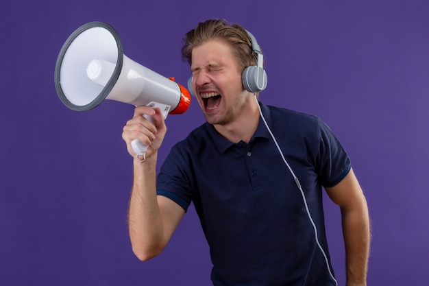 Молодой красавец с наушниками кричит через мегафон, стоя на фиолетовом фоне