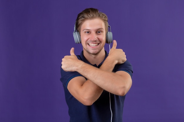 Young handsome man with headphones standing with arms crossed showing thumbs up smiling cheerfully over purple background