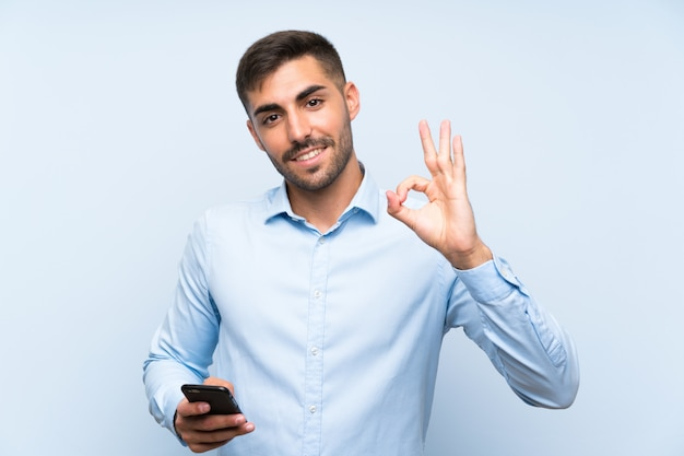 Young handsome man with his mobile over isolated blue wall showing ok sign with fingers