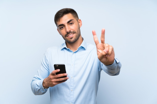 Young handsome man with his mobile over isolated blue wall smiling and showing victory sign