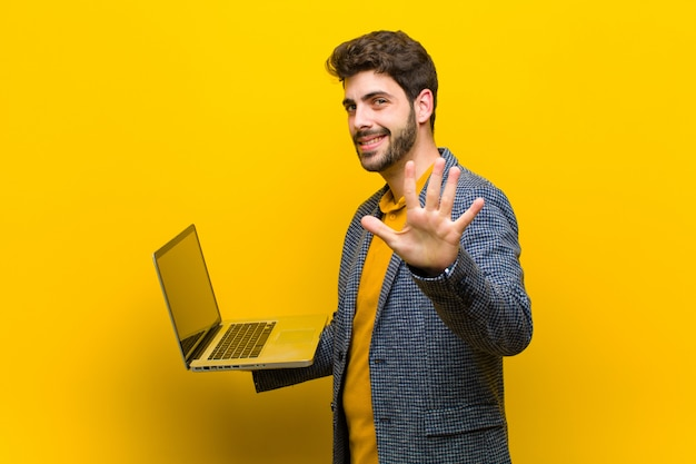 Young handsome man with a laptop against orange background