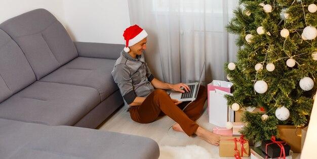 Молодой красавец с ноутбуком в рождественской обстановке дома.