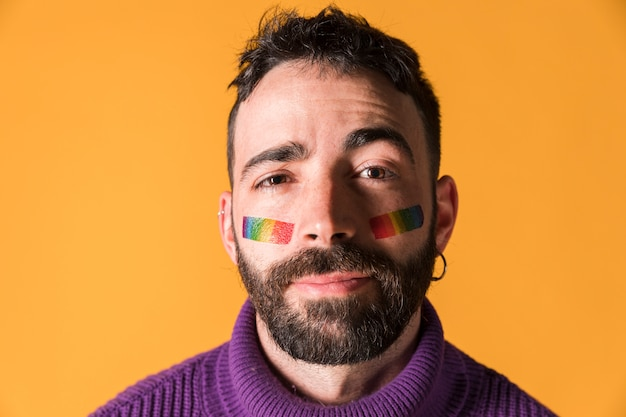 Young handsome man with lgbt symbol on face
