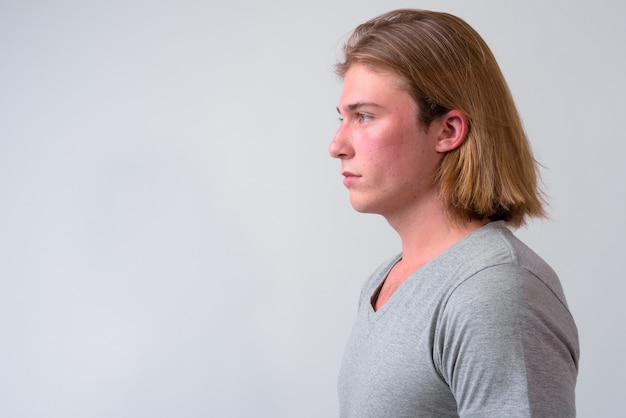 Young handsome man with long blond hair against white wall