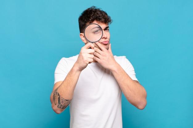 虫眼鏡で若いハンサムな男