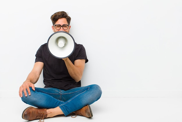 Young handsome man with a megaphone sitting on the floor sitting on the floor in a white room