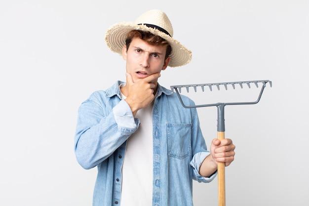 Молодой красавец с широко открытыми глазами и ртом, положив руку на подбородок. концепция фермера