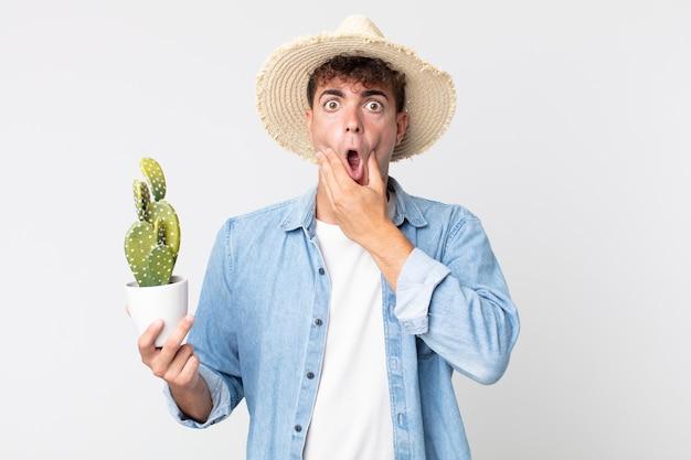 Молодой красивый мужчина с широко открытыми глазами и ртом, положив руку на подбородок. фермер держит декоративный кактус