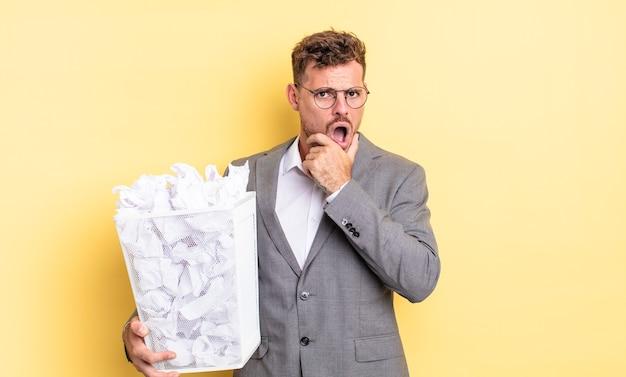 Молодой красавец с широко открытыми глазами и ртом и рукой на подбородке бумажные шарики мусор концепция