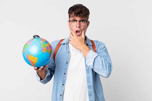 Молодой красавец с широко открытыми глазами и ртом, положив руку на подбородок. студент держит карту мира