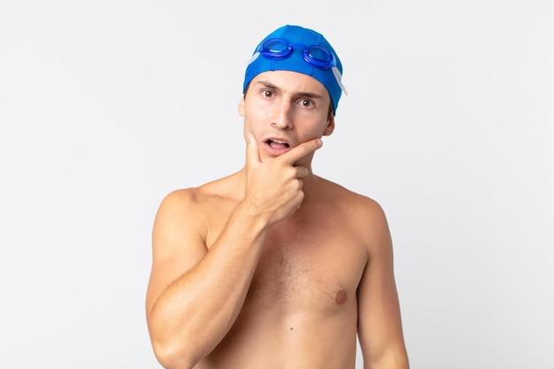Молодой красавец с широко открытыми глазами и ртом, положив руку на подбородок. концепция пловца
