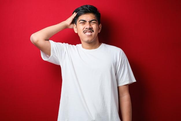 빨간 배경 위에 서 있는 흰색 티셔츠를 입은 콧수염을 기른 젊고 잘생긴 남자는 질문에 대해 혼란스럽고 궁금해합니다. 머리에 손을 얹고 생각하는 불확실한 의심. 잠겨있는 개념.