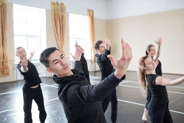 Молодой красавец с вытянутыми руками делает одно из танцевальных упражнений